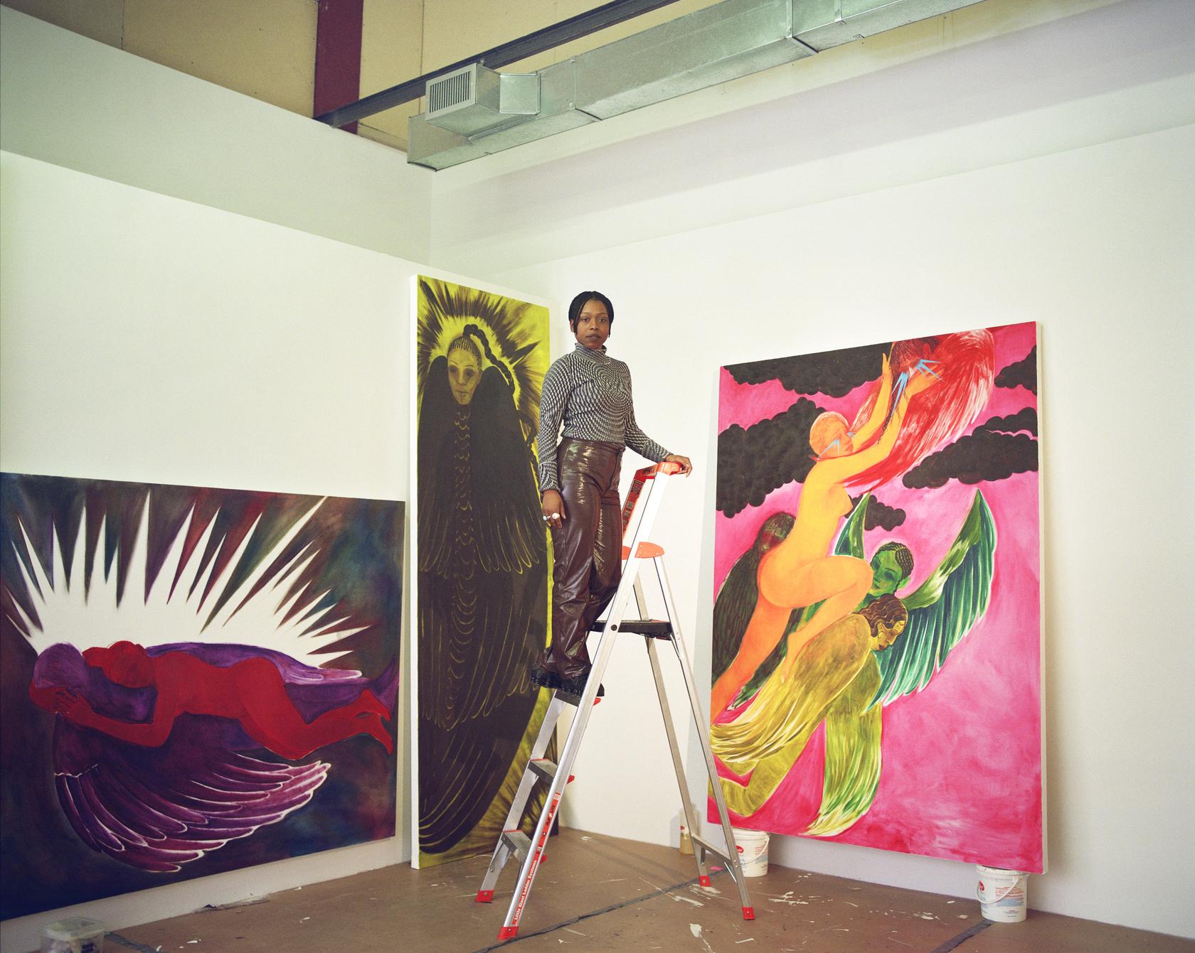 Naudline Pierre standing on a ladder in her studio