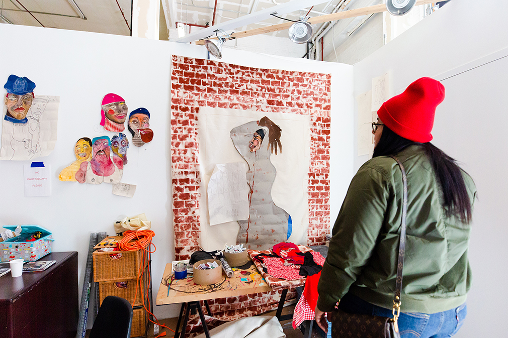A visitor looking at Tschabalala Self's artwork during the Museum's open studios