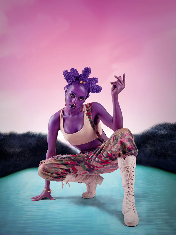 Woman with purple painted skin and purple hair crouching on a light blue ground with pink sky