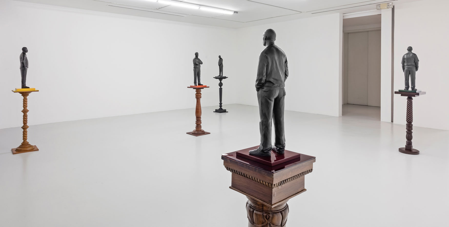 Brass statues of people standing on pedestals throughout an all white room.