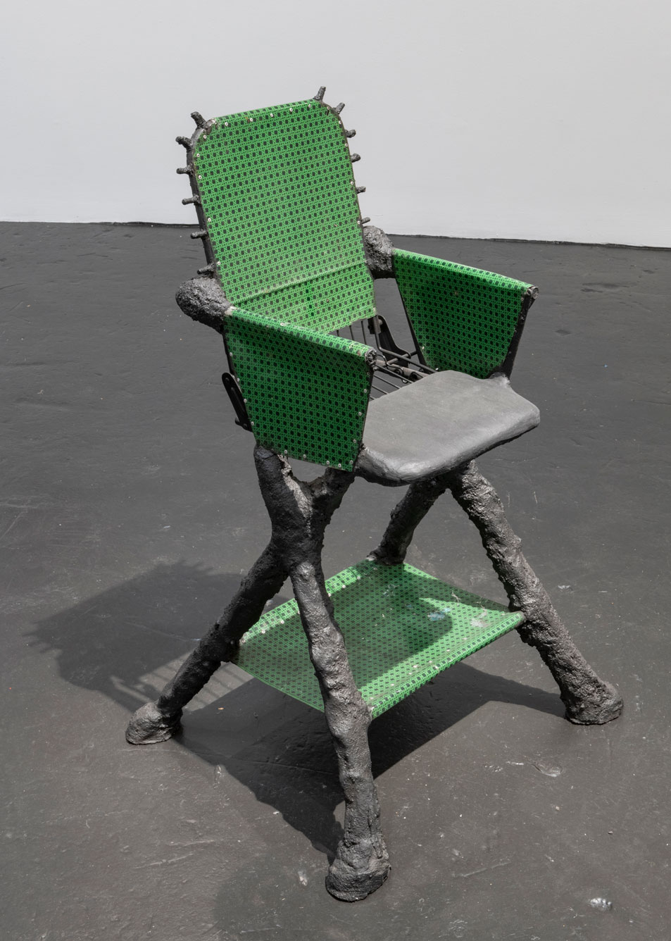 High chair with green netting on a charcoal grey base with bumpy legs