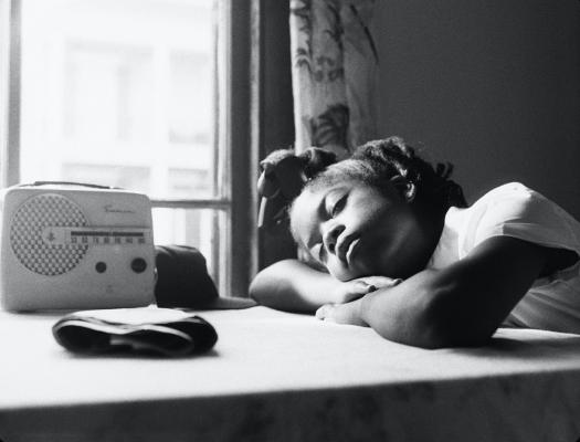A young Black schoolgirl rests in the sunlight by a window with an old-time radio.
