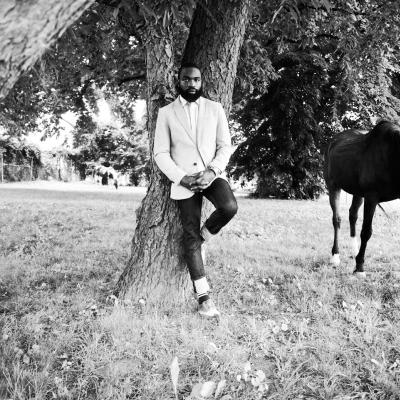 A black and white photograph of a black man leaning against a large tree in a field with a grazing black horse.